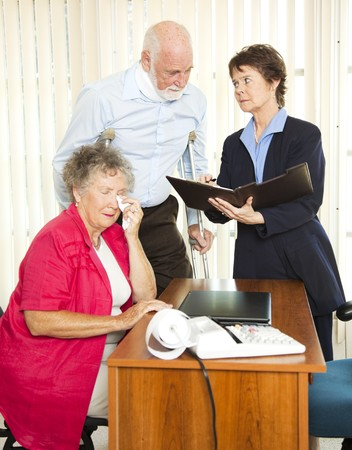 Injured senior man and his upset wife meet with a personal injury lawyer.   photo