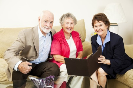 meets: Pretty saleswoman meets with happy senior couple in their home.