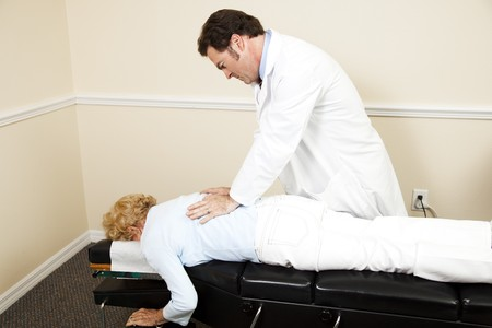 Chiropractor adjusting a senior womans back.  Room for text