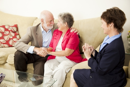 Therapist looks on as a senior couple she's been counseling works out their issues.   Imagens