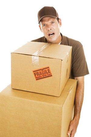 Frustrated delivery man or mover carrying two large boxes.  Isolated on white.  photo