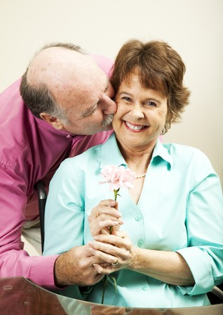 gives: Handsome older man gives a flower to his beautiful wife.   Stock Photo