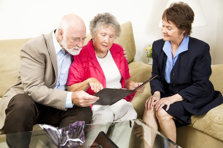 Sales woman looks on as a senior couple considers her product information.  photo