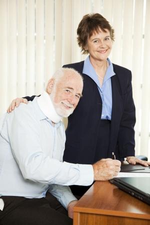 Injured senior man signing paperwork in his attorneys office.