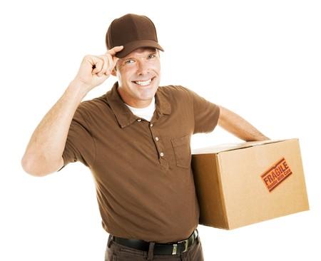 Homme de livraison poli ou déménageur basculage son chapeau et souriant. Isolé sur fond blanc.  Banque d'images