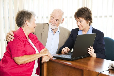 Senior couple with their financial advisor, going over their retirement income on her computer.
