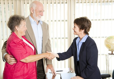 Senior couple meets with a friendly financial adviser.