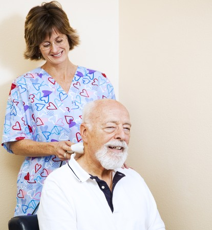 Senior man gets pain relief from a chiropractic nurse using an ultrasound machine.   Stock Photo