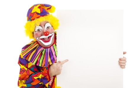Cheerful birthday clown points at a black white sign.  Isolated. photo