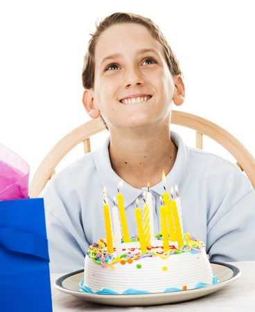 Cute little boy making a birthday wish before blowing out the candles on his cake.  White background.