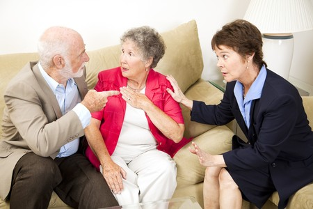 Senior couple in marriage counseling argues in front of their therapist.