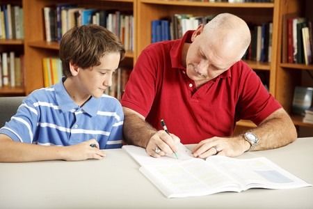 helps: Father helps his son with homework, in the library.   Stock Photo