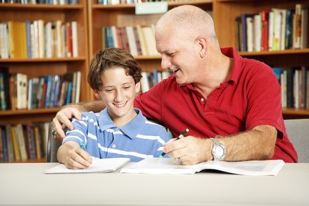 Father helping with his son's homework, in the school library. Stock Photo - 7979348