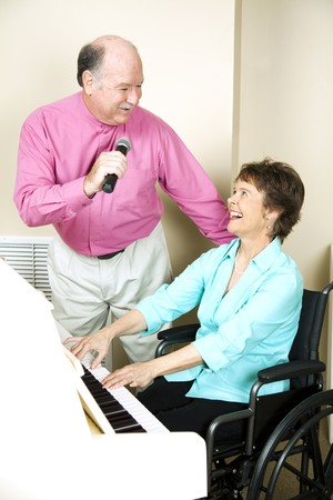 Senior man sings to a pianist in a wheelchair.   photo