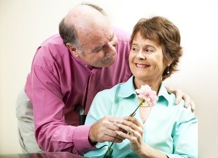 Senior man gives his beautiful wife a flower.   photo