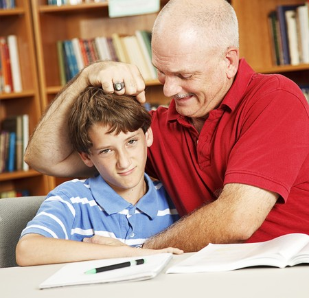 Father takes a break from helping his son with homework to give him noogies. Stock Photo - 7979344