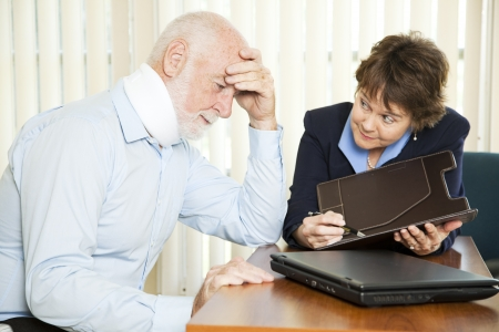 medical bills: Injured senior man and his accountant worrying about the cost of medical bills. Stock Photo