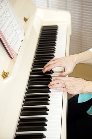 hymnal: Closeup of a church pianists hands as she plays from the hymnal.   Stock Photo