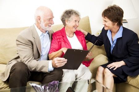 Senior paar luistert naar een verkoopster of financieel consultant in hun huis.   Stockfoto