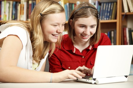netbook: Two teenage girls using a netbook computer in the school library.