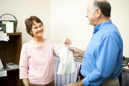 Friendly store clerk hands a customer his bag with a smile. Room for text  Stock Photo - 7979332