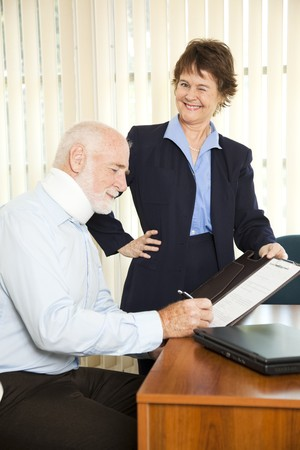 gullible: Personal injury lawyer winks as she signs a gullible client. Stock Photo