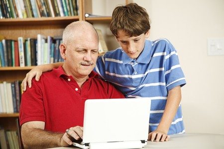 Little boy helping his middle-aged father use the computer.   Stock Photo - 7995024