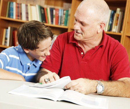 Little boy and his teacher or father in the library doing homework and laughing together. Stock Photo - 7995028
