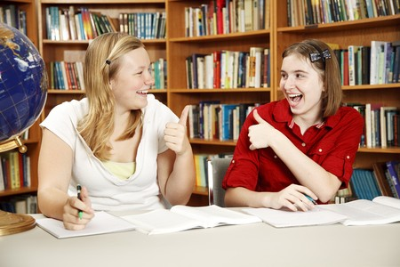 Teen girls doing their homework in the school library and giving each other the thumbs-up sign.   photo