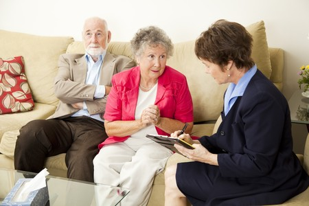 Senior couple in marriage counseling.  The wife talks while the counselor takes notes.   photo
