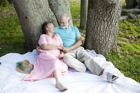 Romantic senior couple relaxes outdoors in the park.   photo