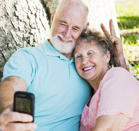 Cute senior couple taking their self portrait with their cellphone.  He's giving her rabbit ears. 스톡 콘텐츠 - 7995026