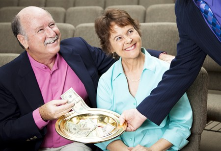 collections: Couple placing money in a church collection plate.