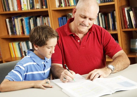 Father helping his young son do homework at the library.   Stock Photo - 8098026