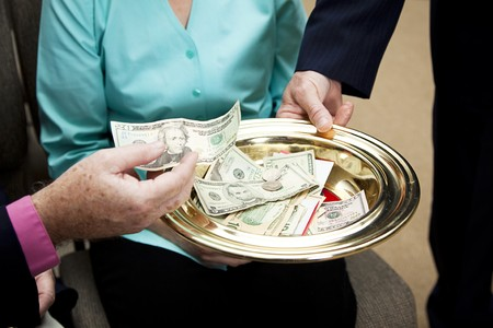 Church members putting money in the collection plate.   Stock Photo