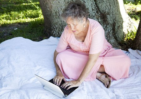 netbook: Senior woman using her netbook laptop computer outdoors.