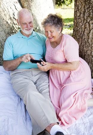 Senior couple reading e-mail on their smart phone.   photo