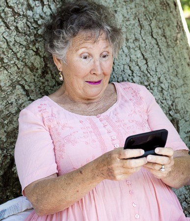 Senior woman receives a surprising text message on her smart phone.   photo