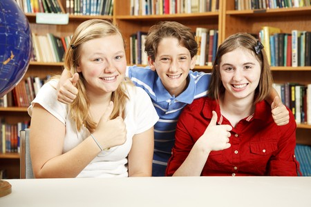 Three school kids in the library, giving thumbs up for education.   photo