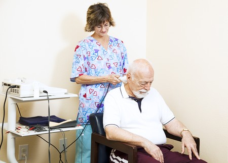 Chiropractic nurse treats a patient's neck with ultrasound therapy.   photo