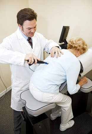 osteopath: Chiropractor using an eletrical tool and computer to diagnose and adjust a patients spine alignment. Stock Photo