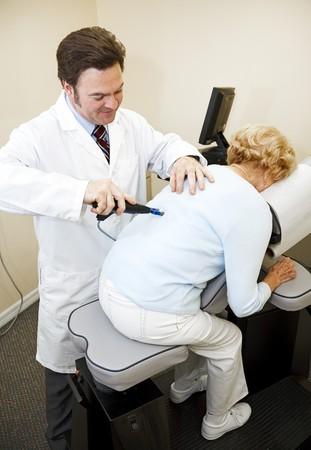 alineaci�n: Quiropr�ctico utilizando una herramienta de eletrical y el equipo para diagnosticar y ajuste de la alineaci�n de columna vertebral de un paciente.