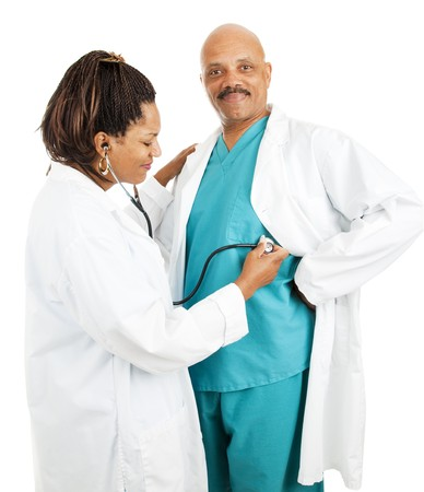 Cute african-american doctors.  She's pretending to give him a checkup.  Isolated on white.   Stock Photo - 8172054