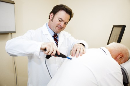 Chiropractor uses and computerized electronic tool to diagnose and adjust a patients spine problems.   photo