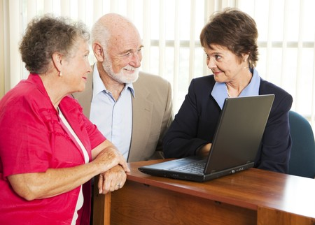 Senior couple meet with a sales woman or financial consultant.   photo