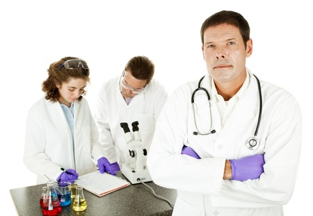 Serious doctor in medical laboratory with researchers in the background.   photo