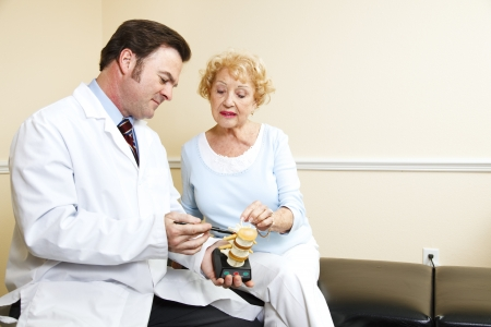 Chiropractor using a plastic model to explain treatment to his patient. Stock Photo - 8240752