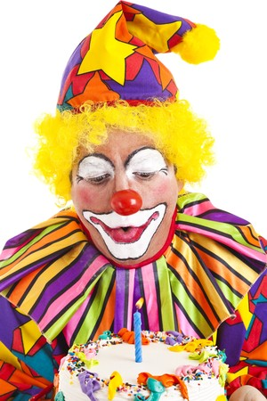 Clown makes a wish and blows out the candle on his birthday cake.   photo