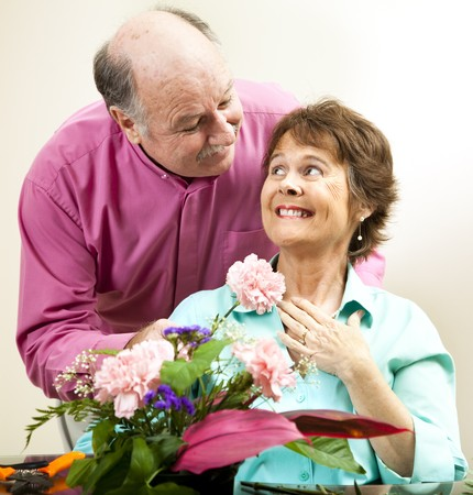 Handsome mature man presents flowers to his beautiful wife.   photo