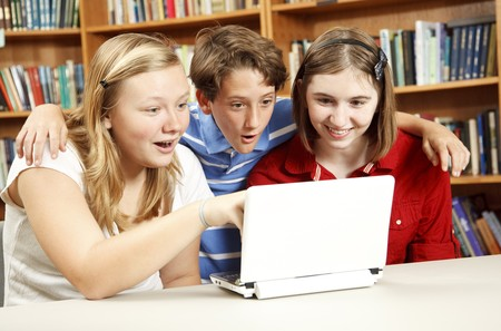 Kids in the school library, using the computer, are surprised by what they are learning.   photo